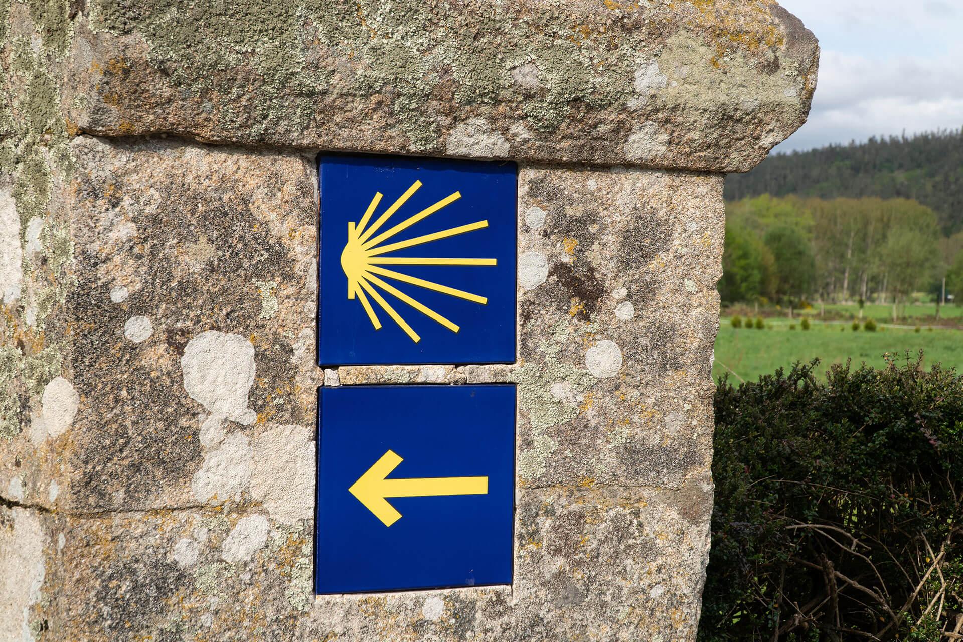Pilgerweg-Plakette an einer Wand