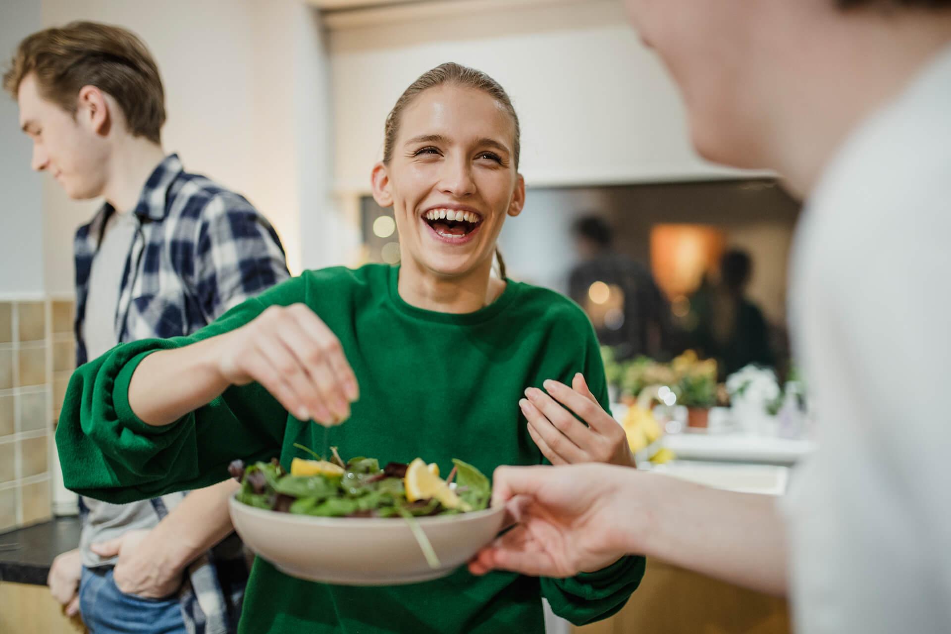 Frau mit Salatteller beim WG-Kochen