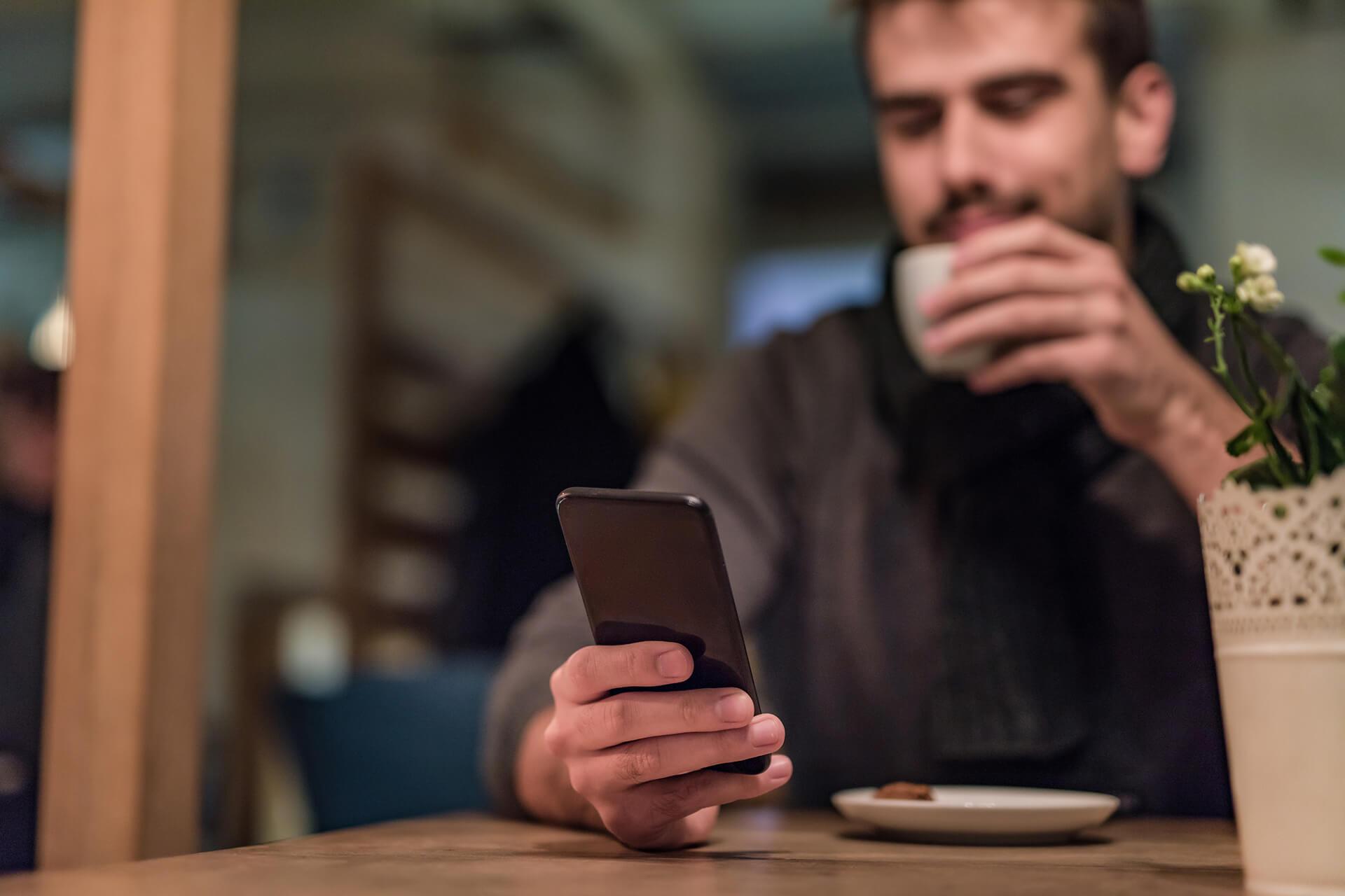Mann sitzt im Café mit Handy