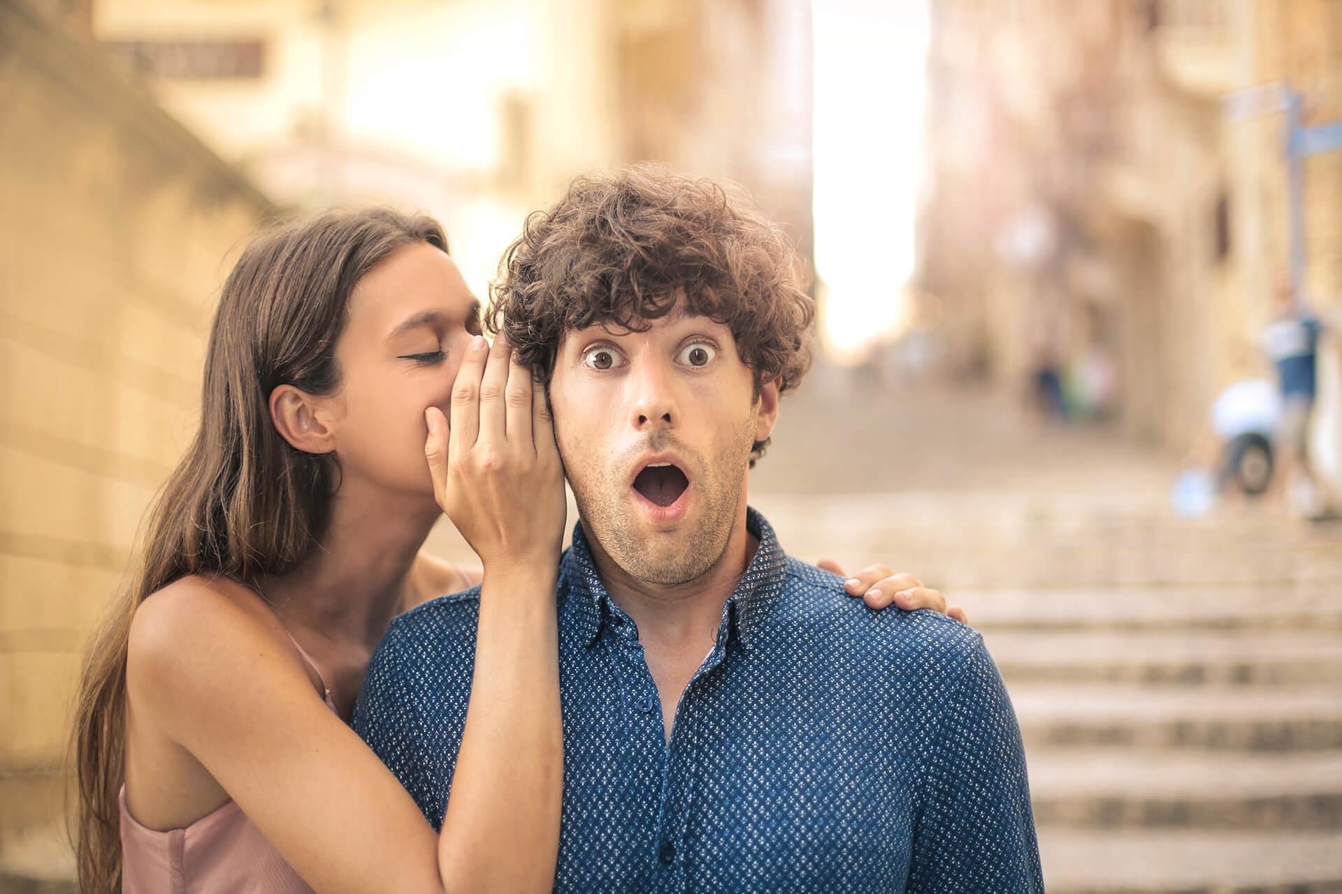 Frau flüstert Mann etwas ins Ohr, der über das Gehörte überrascht ist