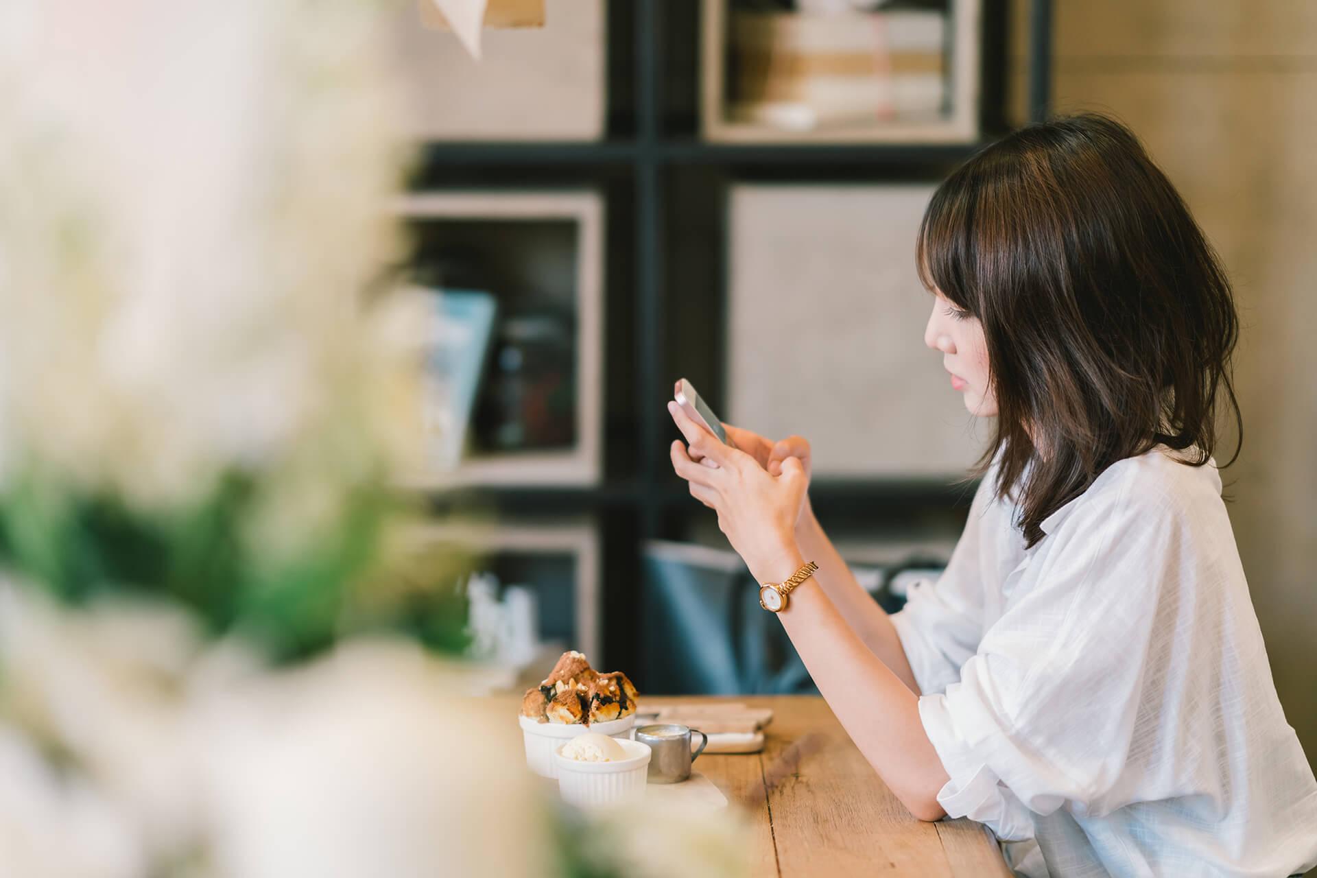 Frau sitzt im Café mit Handy