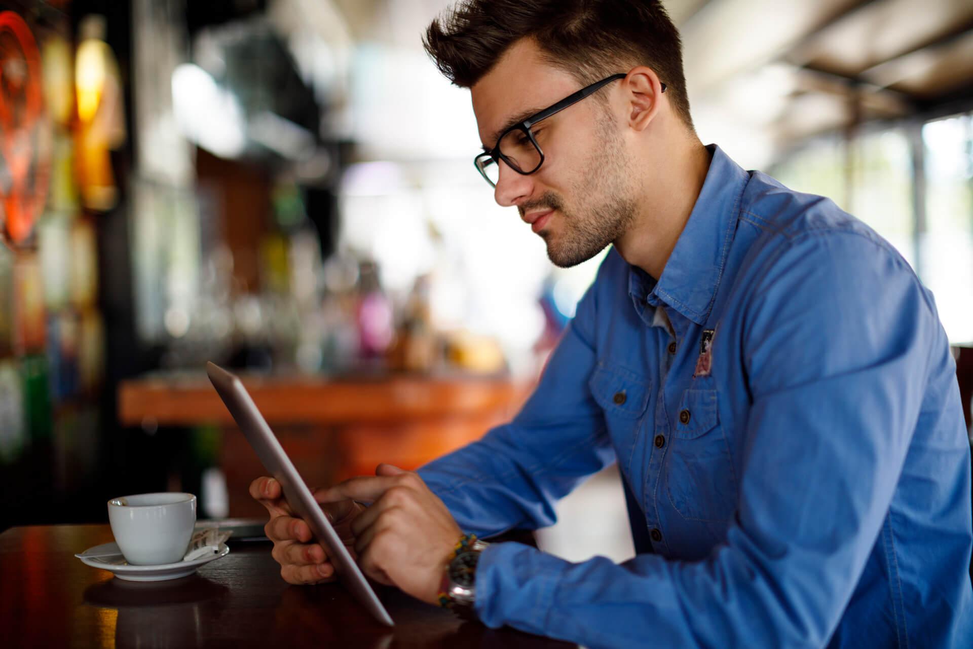 Junger Mann liest etwas im Tablet in einem Café