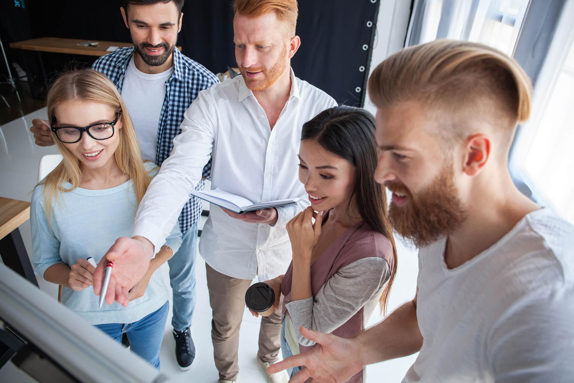 Ein junges Team ararbeitet ein Projekt an einem Flip-Chart